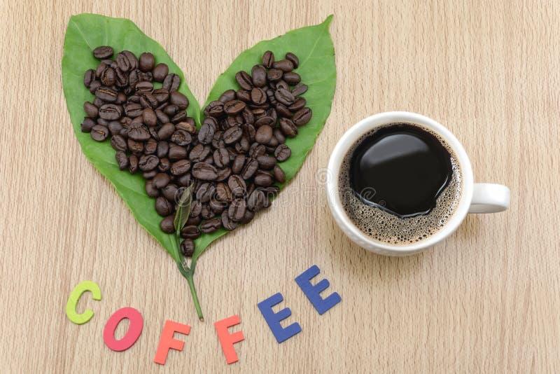 咖啡杯用咖啡豆和咖啡叶子 图库摄影