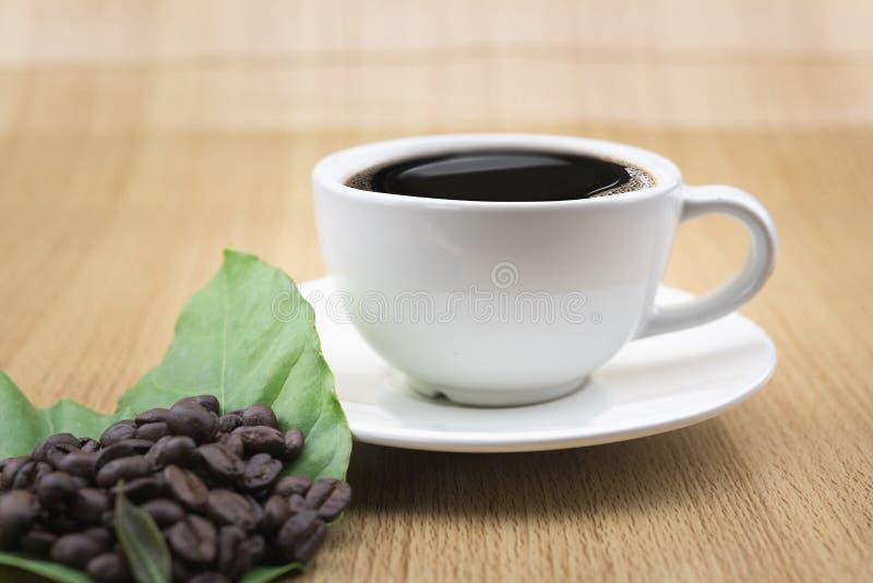 咖啡杯用咖啡豆和咖啡叶子 库存照片