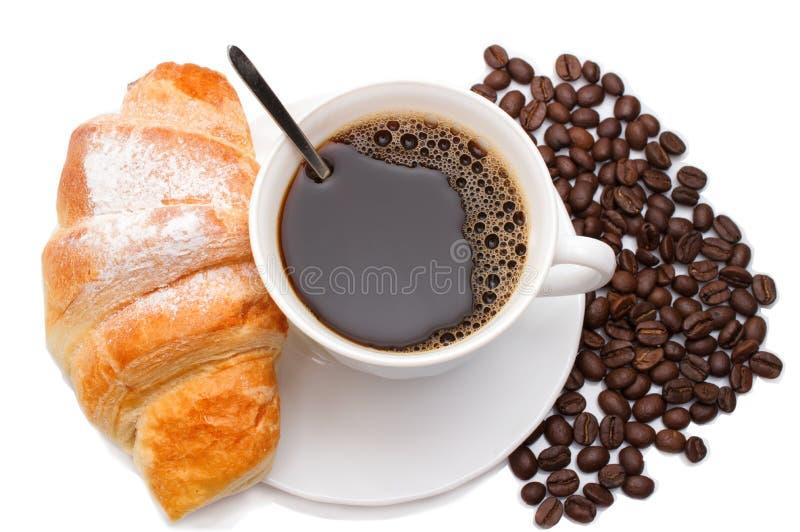 咖啡杯用新月形面包和咖啡豆在白色背景 库存图片