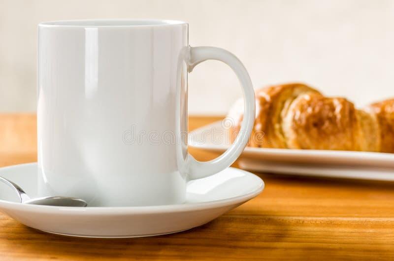 咖啡杯用新月形面包 免版税库存图片