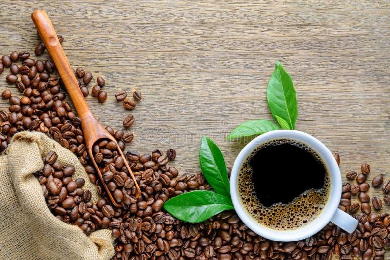 咖啡杯用豆、木匙子、大麻大袋袋子和绿色叶子在木桌上 免版税库存照片