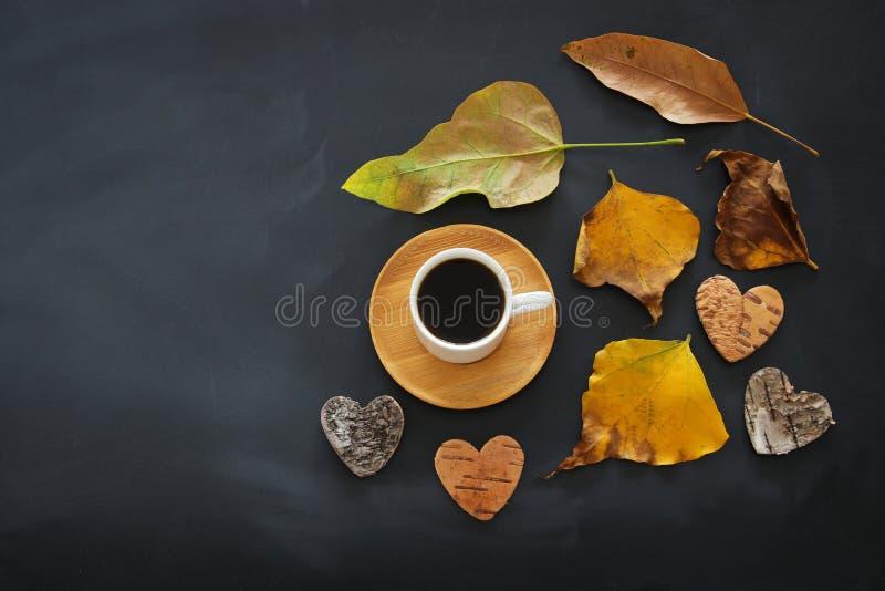 咖啡杯的顶视图图象在黑板背景和干燥秋叶的 免版税库存照片