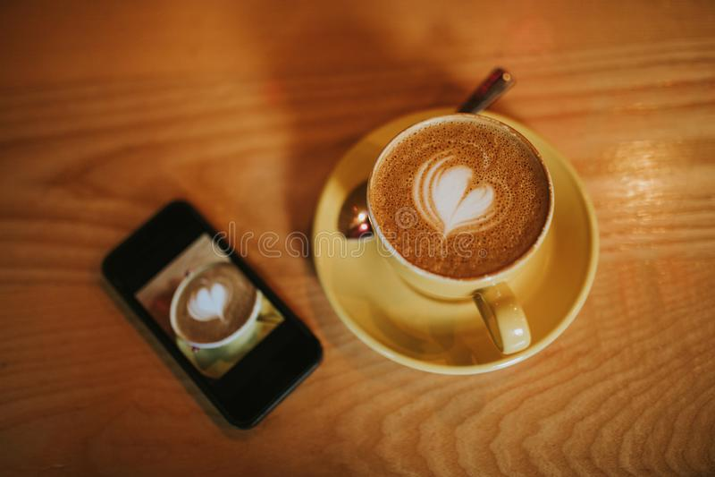 咖啡杯移动电话 免版税图库摄影