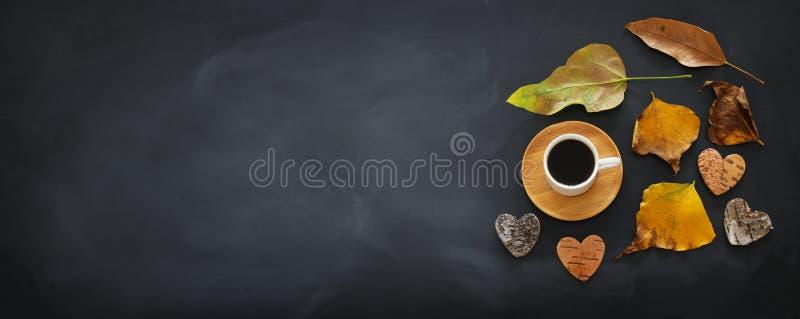 咖啡杯顶视图横幅在黑板背景和干燥秋叶的 免版税库存照片