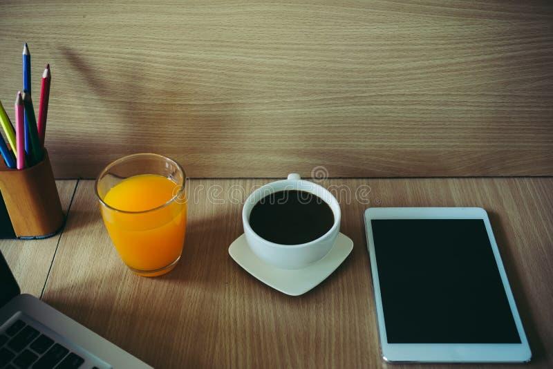 咖啡杯,片剂,在书桌上的橙汁的图象 图库摄影