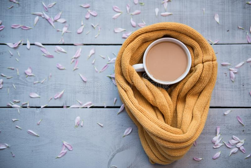 咖啡杯,饼干,花瓣,编织了在一张木桌上的黄色围巾 免版税库存照片