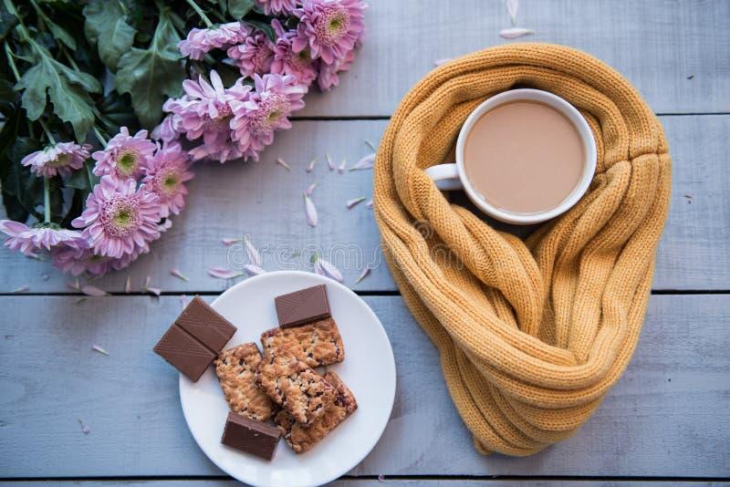 咖啡杯,饼干,花瓣,编织了在一张木桌上的黄色围巾 库存图片
