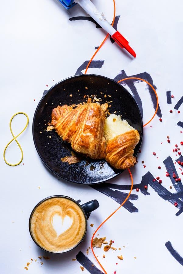咖啡杯cappucino艺术用新近地被烘烤的新月形面包早餐 库存照片