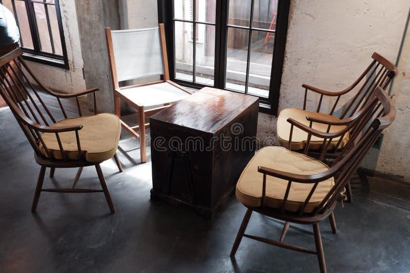 咖啡桌和椅子在窗口附近与顶楼样式 免版税库存照片