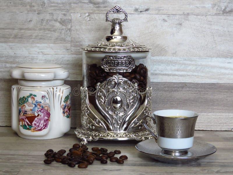咖啡瓶子和一杯咖啡在被漂白的橡木木架子瓷和玻璃银色葡萄酒英镑的 免版税库存照片