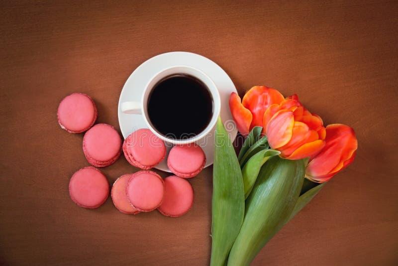 咖啡用桃红色蛋白杏仁饼干和郁金香开花 图库摄影
