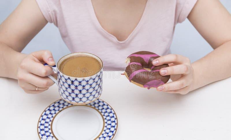 咖啡用牛奶、一个多福饼用巧克力和桃红色结冰,妇女的手 免版税图库摄影