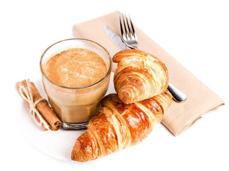 咖啡用牛奶和新月形面包在白色板材和亚麻布餐巾 免版税图库摄影