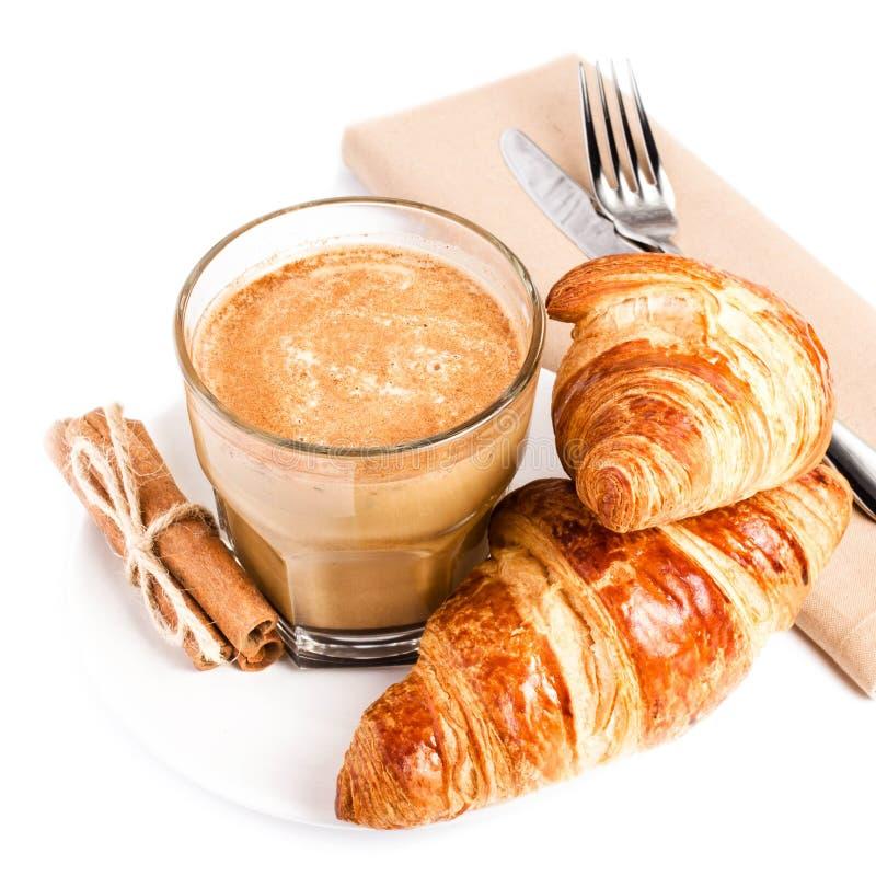 咖啡用牛奶和新月形面包在白色板材和亚麻布餐巾 图库摄影
