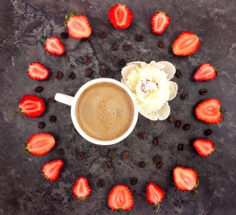 咖啡的五颜六色的明亮的构成,草莓和牡丹开花 免版税库存照片