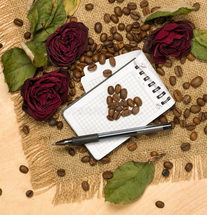 从咖啡种子的心脏形状在空白纸和英国兰开斯特家族族徽 图库摄影