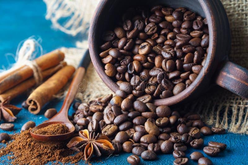 咖啡粒倾吐在黏土杯子外面和驱散在蓝色质地背景、茴香星、肉桂条和地面 库存照片