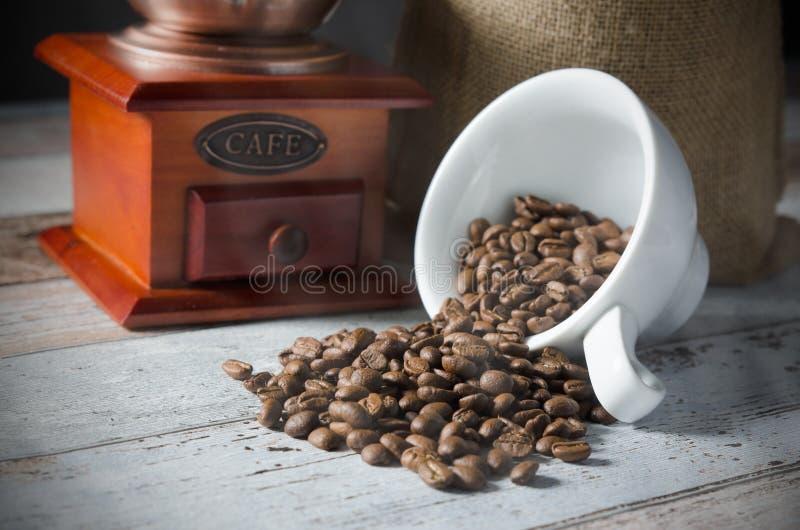 咖啡粒从杯子溢出 黄麻袋子烤豆 免版税库存照片