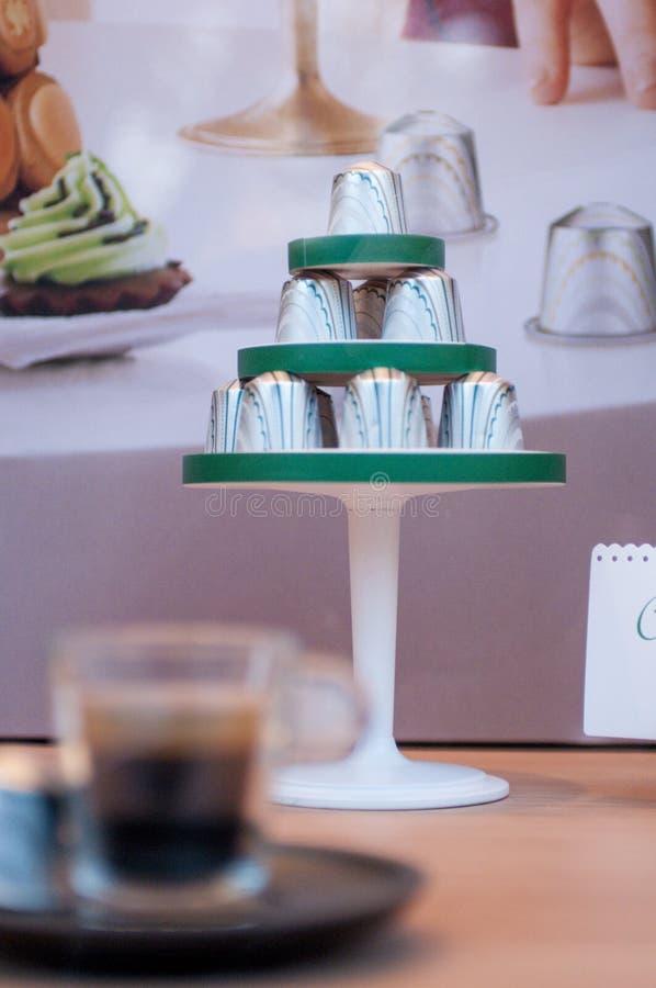 咖啡胶囊金字塔与杯的在前景的咖啡 免版税库存照片