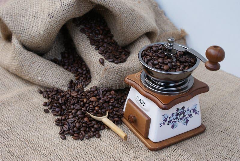 咖啡袋用烤咖啡豆填装了在老磨咖啡器旁边 免版税库存照片