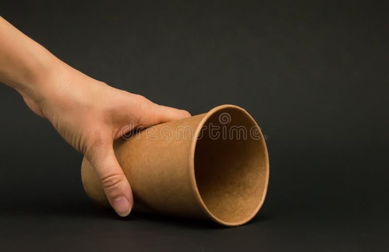 咖啡谎言的空的纸杯在它的在黑背景的边,落玻璃,拿着一纸杯的手 免版税图库摄影
