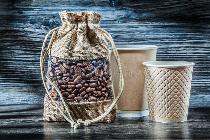 咖啡豆吮和纸杯 免版税库存照片