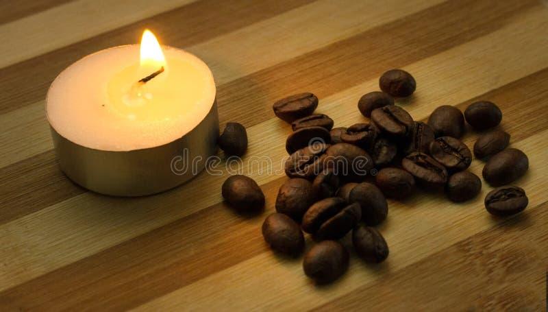 咖啡豆和一个被点燃的蜡烛 库存照片