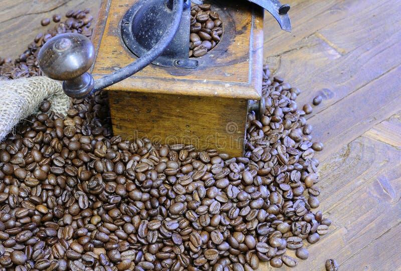 咖啡豆和减速火箭的研磨机在木桌上 库存图片