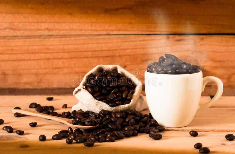 咖啡豆和咖啡与烟的在木桌ba 图库摄影
