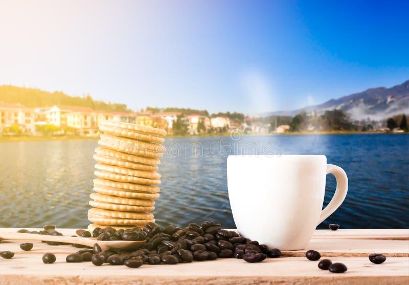 咖啡豆和咖啡用在木桌上的薄脆饼干 免版税库存照片