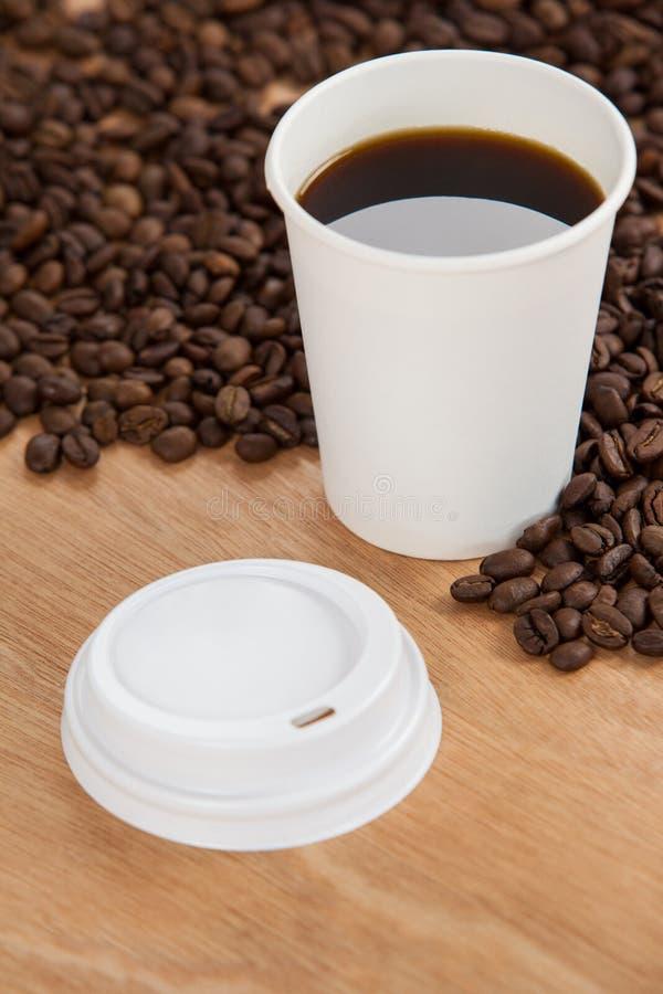 咖啡豆和无奶咖啡在一次性杯子 库存图片
