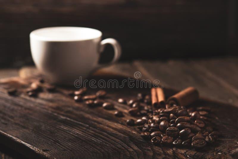 咖啡豆和白色杯子在木黑暗的背景 库存照片