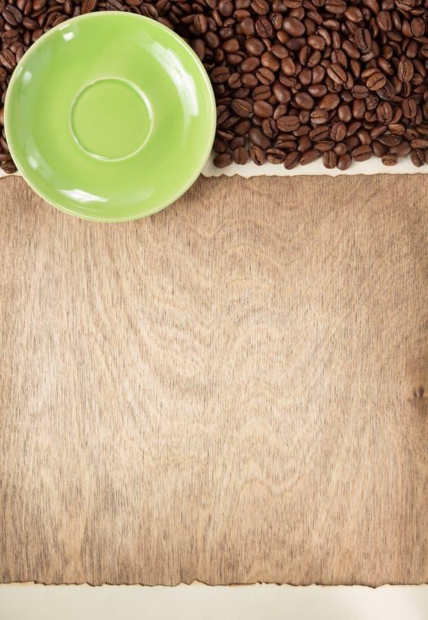 咖啡豆和茶碟在木背景 免版税图库摄影