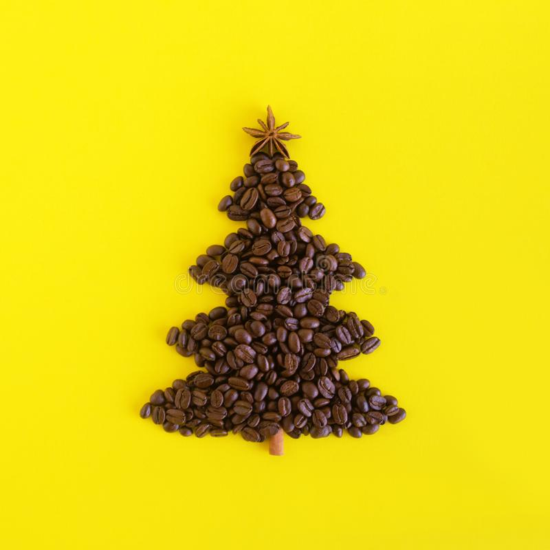 咖啡豆和装饰的茴香星和肉桂条做的圣诞树在黄色背景,平的位置 免版税库存图片