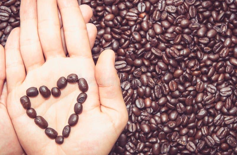咖啡豆在手顶部的心脏标志 库存图片