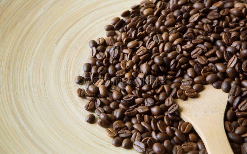咖啡豆在米黄竹板材,特写镜头驱散了 免版税库存照片