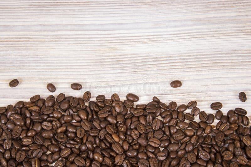 咖啡豆大模型在被隔绝的木织地不很细背景的 库存图片