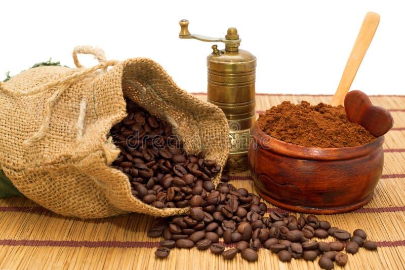 咖啡豆溢出了在袋子、碾碎的咖啡在碗,匙子、一点心脏和磨咖啡器外面 免版税图库摄影