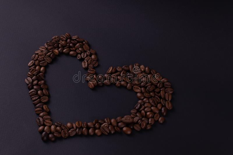 咖啡豆的不对称的等高心脏在左角的 图库摄影