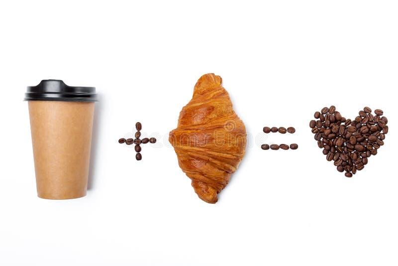 咖啡豆的心脏与纸在白色背景隔绝的咖啡杯和新月形面包的 库存图片