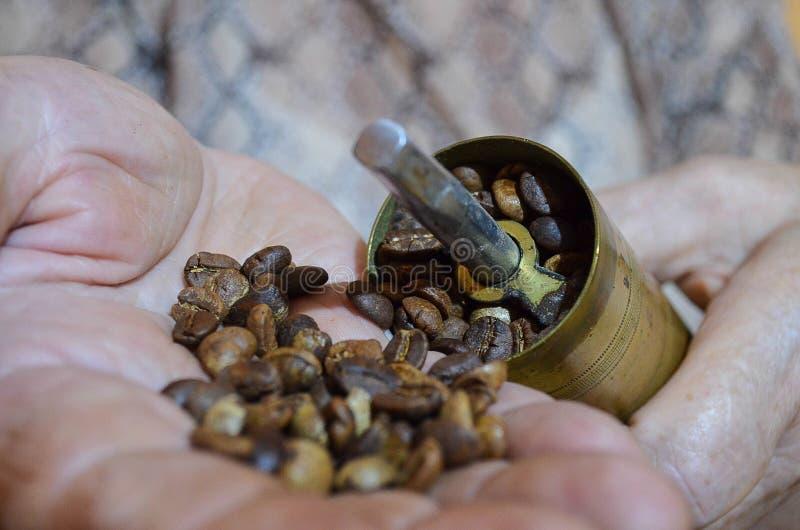 咖啡豆的老咖啡碾和手傻瓜 免版税图库摄影