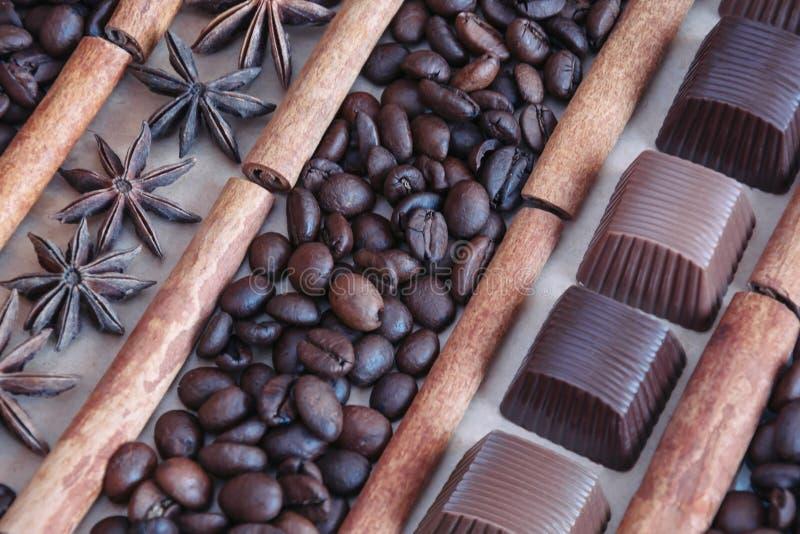咖啡豆背景用巧克力、茴香星和肉桂条 库存图片