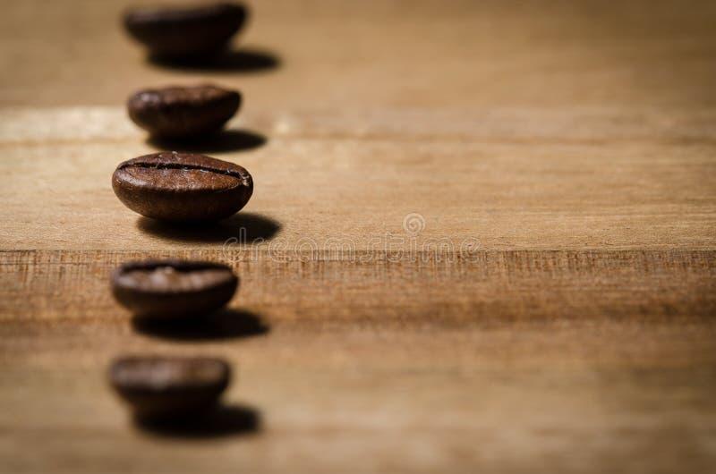 咖啡豆连续在木头 免版税库存照片