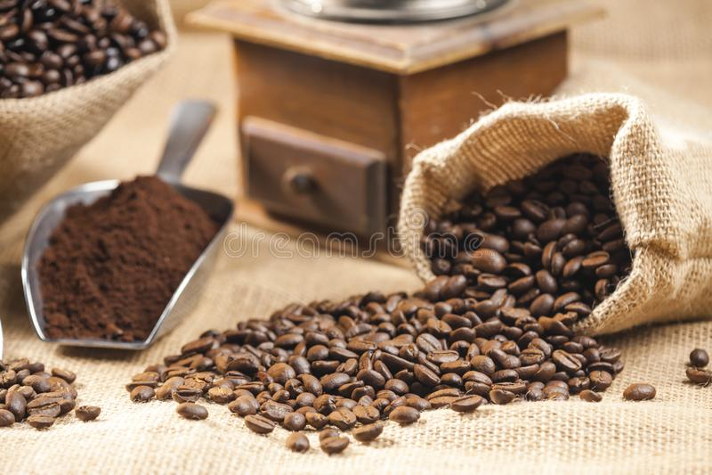 咖啡豆静物画在黄麻袋子的与磨咖啡器 免版税图库摄影