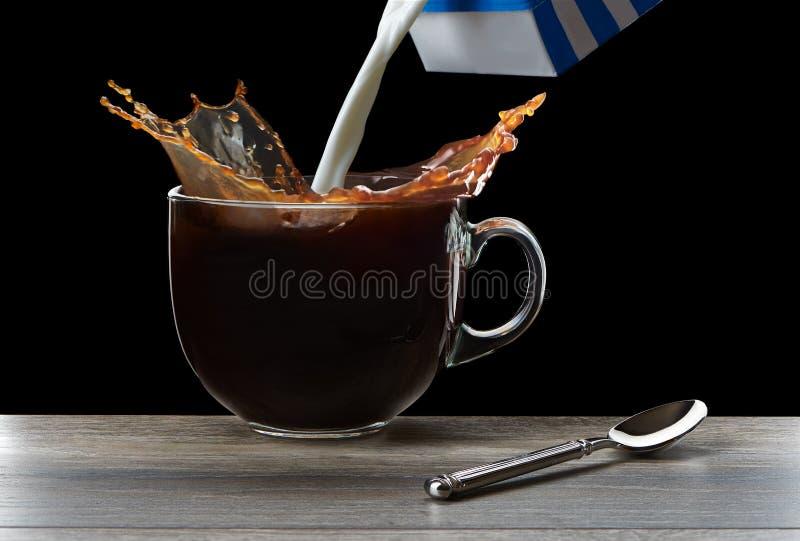咖啡飞溅在杯子的在桌上 图库摄影