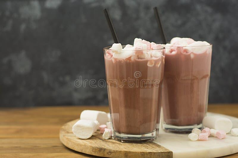 咖啡饮料、可可粉与巧克力汁香草奶油和蛋白软糖在木桌和grounge背景 库存图片
