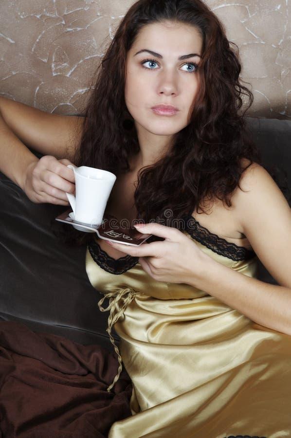 咖啡饮用的女孩年轻人 免版税库存照片