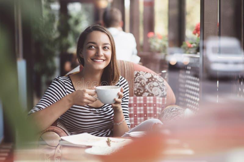 咖啡饮用的妇女年轻人 免版税库存照片