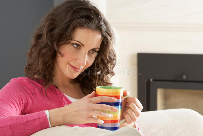 咖啡饮用的家庭松弛沙发妇女 免版税库存图片