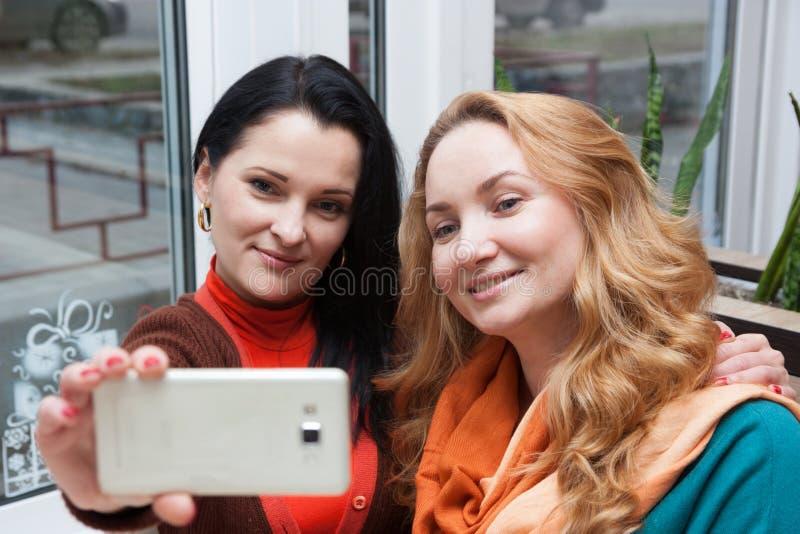咖啡馆和selfie的愉快的妇女 免版税库存照片